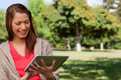 Young woman smiling enthusiastically while using a tablet Royalty Free Stock Photo