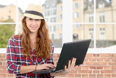 Young woman with smiling face holding laptop. A young woman with smiling face holding laptop stock photography