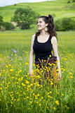 Young woman smiling in a field of flowers Royalty Free Stock Photo