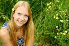 Young Woman Smiling in Flowers. A young, attractive woman, sitting in the grass and flowers, looks up at the camera and smiles Stock Photos