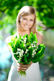 Young woman smiling and give a bouquet of flowers Royalty Free Stock Photography