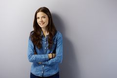 Young woman smiling by grey wall Royalty Free Stock Images