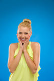 Young woman smiling with hands on chin against blue background. Stock Images