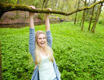 Young woman smiling and hanging on a branch Royalty Free Stock Image