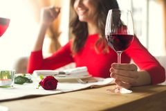 Young couple having romantic dinner in the restaurant. Young woman smiling having romantic dinner in the restaurant wine glass close-up Royalty Free Stock Photography