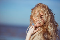 A young woman is smiling, her hair hanging down on her face stock photo