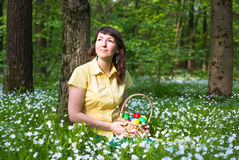 Young woman smiling and holding basket of easter eggs in spring forest Stock Photo
