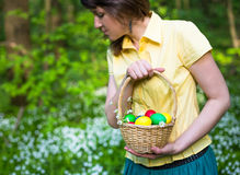 Young woman smiling and holding basket of easter eggs in spring forest Royalty Free Stock Image