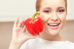 Young woman smiling and holding red pepper Stock Image