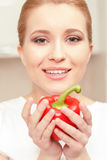 Young woman smiling and holding red pepper Royalty Free Stock Photo