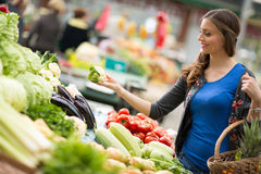 Young woman smiling and holding vegetable at market royalty free stock photo
