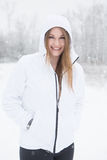 Young woman smiling with hood up standing in snow. Young woman outdoors hiking during a winter snow storm Royalty Free Stock Images