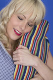 Young Woman Smiling Hugging a Hot Water Bottle with Eyes Shut Royalty Free Stock Photography