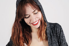 Young woman is smiling so innocently in a hooded jumper. Young woman is smiling so innocently in a grey hooded jumper. Studio shot with light grey background Stock Photo