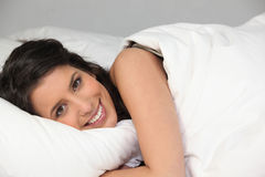 Young woman smiling laid in bed Royalty Free Stock Images