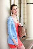 Young woman smiling and leaning against wall with bag Royalty Free Stock Image