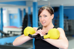 Young woman smiling while lifting kettle bell Stock Image