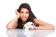 A young woman smiling, with a lily in her hand Stock Photography