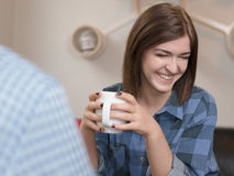 Young woman smiling and looking away. Young woman in conversation, holding a cup of coffee and smilingly looking away Stock Images