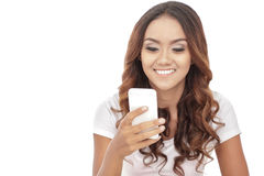 Young woman smiling while looking at her mobilephone. Portrait of young woman smiling while looking at her mobilephone  on white background Royalty Free Stock Image