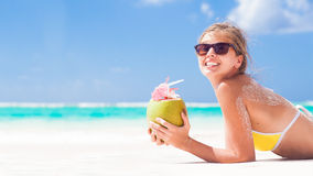 Young woman smiling lying in bikini with coconut Stock Photography