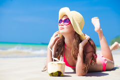 Young woman smiling lying in straw hat in Royalty Free Stock Images