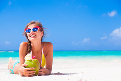 Young woman smiling lying in straw hat in sunglasses with coconut on beach. Remote tropical beaches and countries. travel concept Stock Image