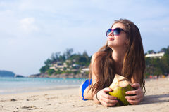 Young woman smiling lying in sunglasses in Royalty Free Stock Image