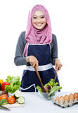 Young woman smiling while making salad. Portrait of young woman smiling while making salad isolated on white Stock Photo