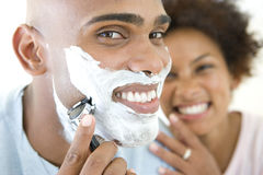 Young woman smiling at man shaving, portrait of man, close-up Stock Image
