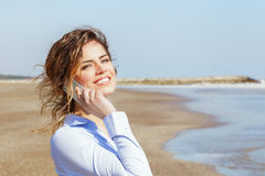Young woman smiling on the mobile phone at the seaside Stock Photography