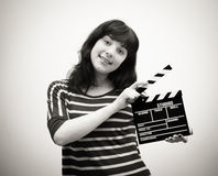 Young woman smiling with movie clapper board Stock Photos