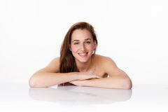 Young woman smiling for natural pampering spa treatment. Haircare concept - happy 20s woman with long brown hair smiling leaning on clear white glass for purity Stock Images