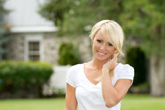 Young Woman Smiling Outside. A young blonde woman outside smiling royalty free stock photo