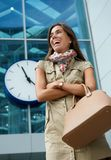 Young woman smiling outside building with clock Stock Image