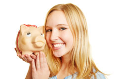 Young woman smiling with piggy bank Stock Images