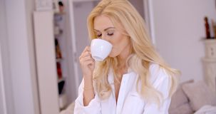 Young woman smiling in pleasure enjoying coffee Royalty Free Stock Images