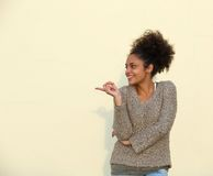Young woman smiling and pointing finger. Portrait of a young woman smiling and pointing finger Stock Photo