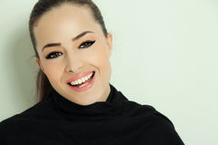 Young woman smiling. Portrait of a young smiling woman with elegant makeup, studio Stock Photography