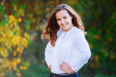 Young woman. Smiling pretty girl posing in colorful autumn park Stock Image