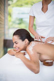Young woman smiling while receiving spa treatment Royalty Free Stock Image