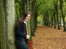 Young woman smiling and relaxing outdoors on an autumn day Royalty Free Stock Photo
