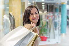 Young woman smiling with shopping bags over the shoulder. Young beautiful woman smiling with shopping bags over the shoulder Royalty Free Stock Photography