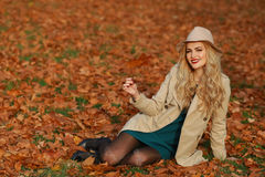Young woman smiling sitting on the grass in the autumn. fall yellow maple garden background. Beautiful girl in coat and floppy hat Stock Images
