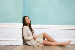 Young woman smiling and sitting on wood floor at home Royalty Free Stock Images