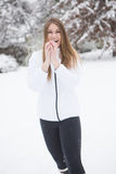 Young woman smiling with snow ball. Young adult woman, making and throwing snowball during a winter snow storm Royalty Free Stock Photography
