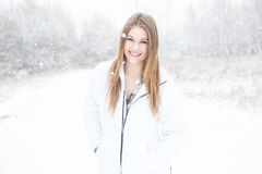 Young woman smiling standing in snow. A young adult woman smiling standing in an open field of snow with a forrest in the background Royalty Free Stock Images