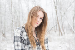 Young woman smiling standing in snow covered forest. Young woman in black and white plaid shirt stading in a snow covered forrest Stock Photography