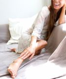 Young woman smiling and stroking legs Stock Photography