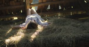 Young woman smiling in the sun rays on the hay. Wooden shed. 4K. stock video
